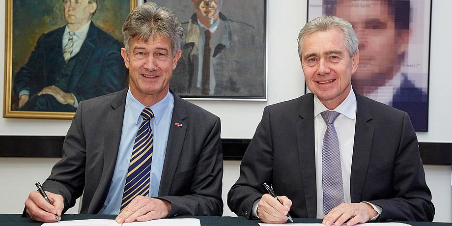 Zwei Herren sitzen vor einem Tisch, beide halten scharze Füllfedern in der Hand und vor ihnen liegt jeweils ein aufgeschlagenes Dokument.