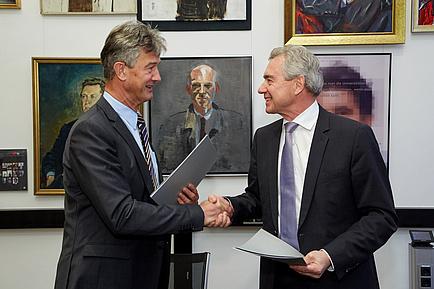 Zwei Herren im Anzug blicken einander an und schütteln sich die Hände. Beide halten eine Dokumentenmappe in der anderen Hand.