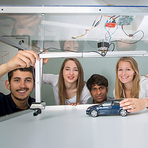 Four young people with a model car and a camera