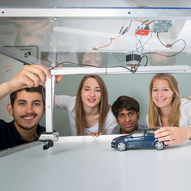 Vier junge Leute mit Modellauto und Kamera