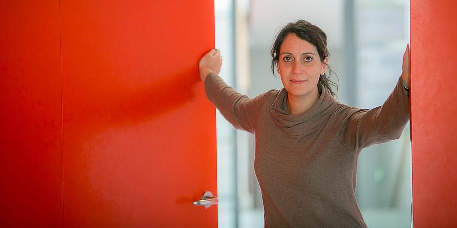 Eine dunkelhaarige Frau mit einem Zopf im Nacken steht in einer offenen Türe. Sie hat eine Hand am linken und eine Hand am rechten Türrahmen. Die Wände rund um die Türe sind rot.