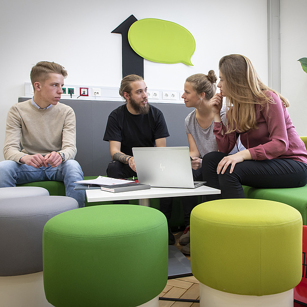 Two young men and two young women sit on green stools and a grey sofa. They talk to each other. On the wall above them is a green speech bubble. On a small table in front of them there is an open laptop.