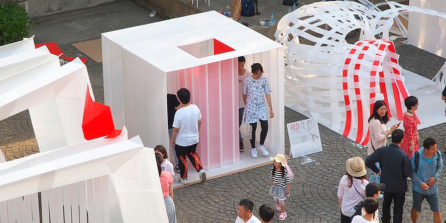 Im Bildzentrum steht ein kleiner, weißer Pavillon aus Polypropylen-Hohlstegplatten auf 2,25 mal 2,25 Metern Grundfläche, mittig im Pavillon ein mit roten Platten verkleideter Patio. Daneben sind weitere Pavillonvarianten ausgestellt. Rundherum chinesische Besucherinnen und Besucher.