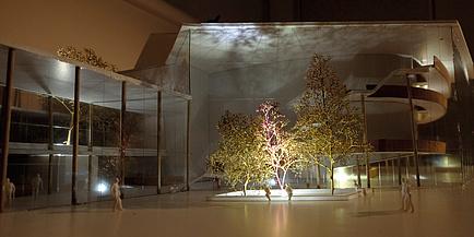 Architekturmodell eines Hauses, davor steht eine Baumgruppe - das Ensemble wir lichttechnisch bespielt