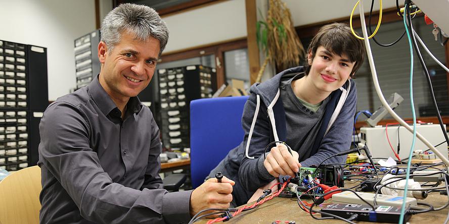 Ein älterer Mann und ein junger Mann sitzen an einem Tisch. Vor ihnen sind viele elektrische Geräte und Kabel zu sehen.