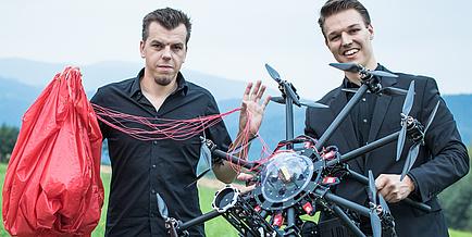 Zwei junge Männer präsentieren ihre Erfindung, einen Rettungsfallschrim für Drohnen. Der Mann rechts im Bild hält eine schwarze Drohne, der Herr links im Bild einen roten Rettungsfallschirm.