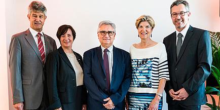 drei Männer und zwei Frauen im Business Outfit  lachen in die Kamera