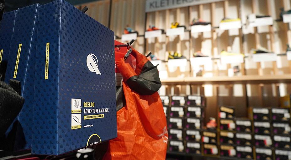Blaue Schachteln mit der Aufschrift REELOQ Adventure Package und einem orangen Sack in einem Sportgeschäft.