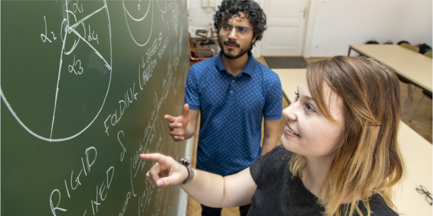 Two students at a blackboard.