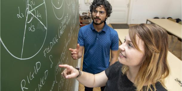 Zwei Studierende an einer Tafel.