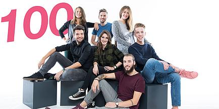 """Eine Gruppe junger Studierender sitzen auf Hockern, links hinten prangt die Zahl """"100"""""""