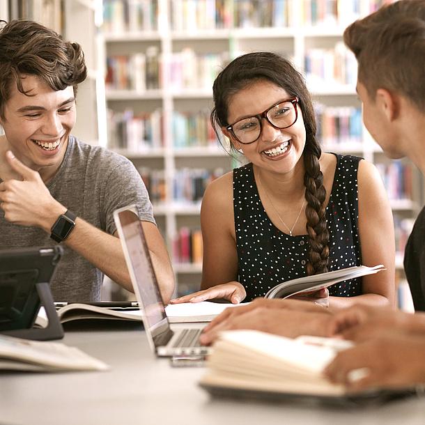3 junge Leute sitzen an einem Tisch vor einem Bücherregal.