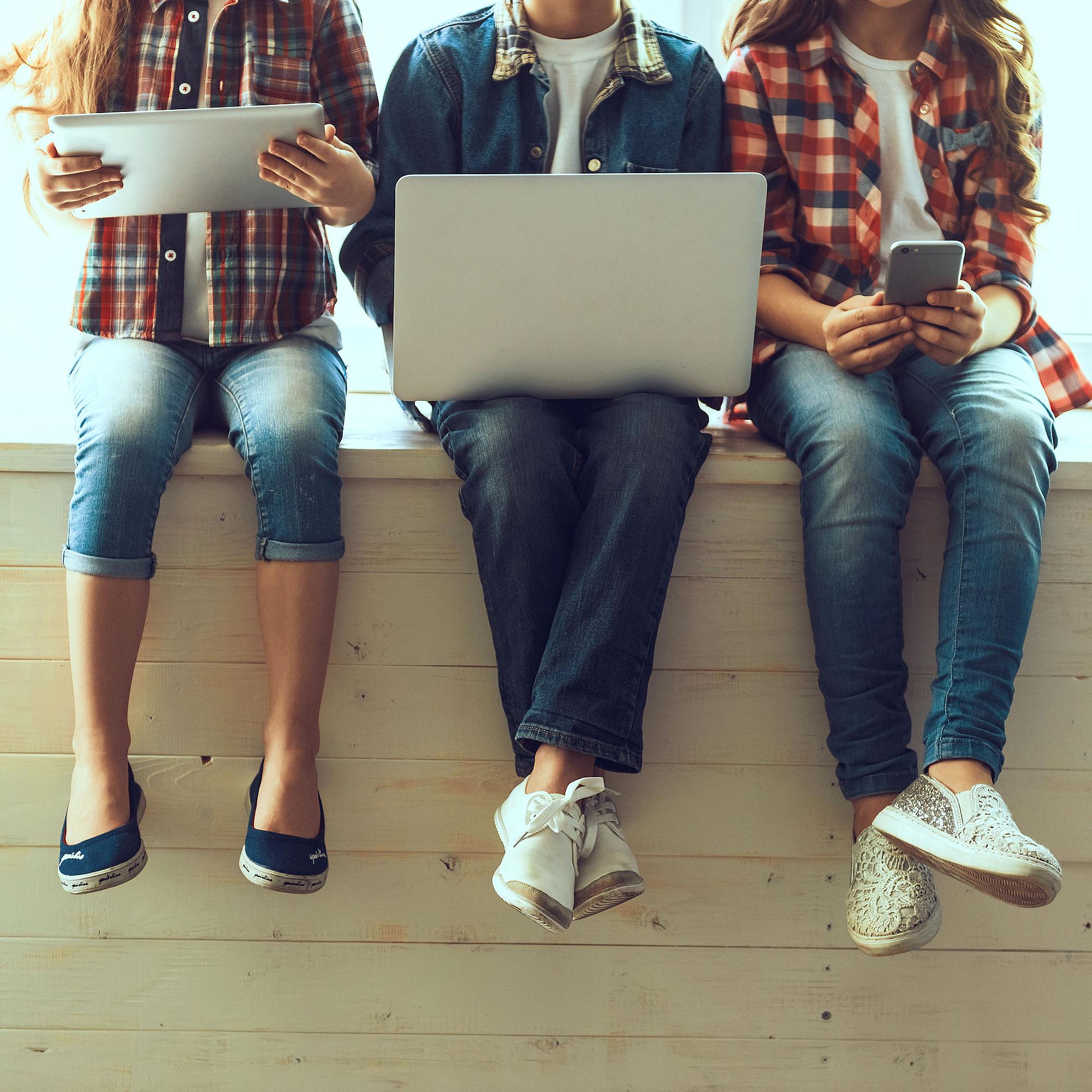 Junge Leute mit Handy, Tablet und Notebook.