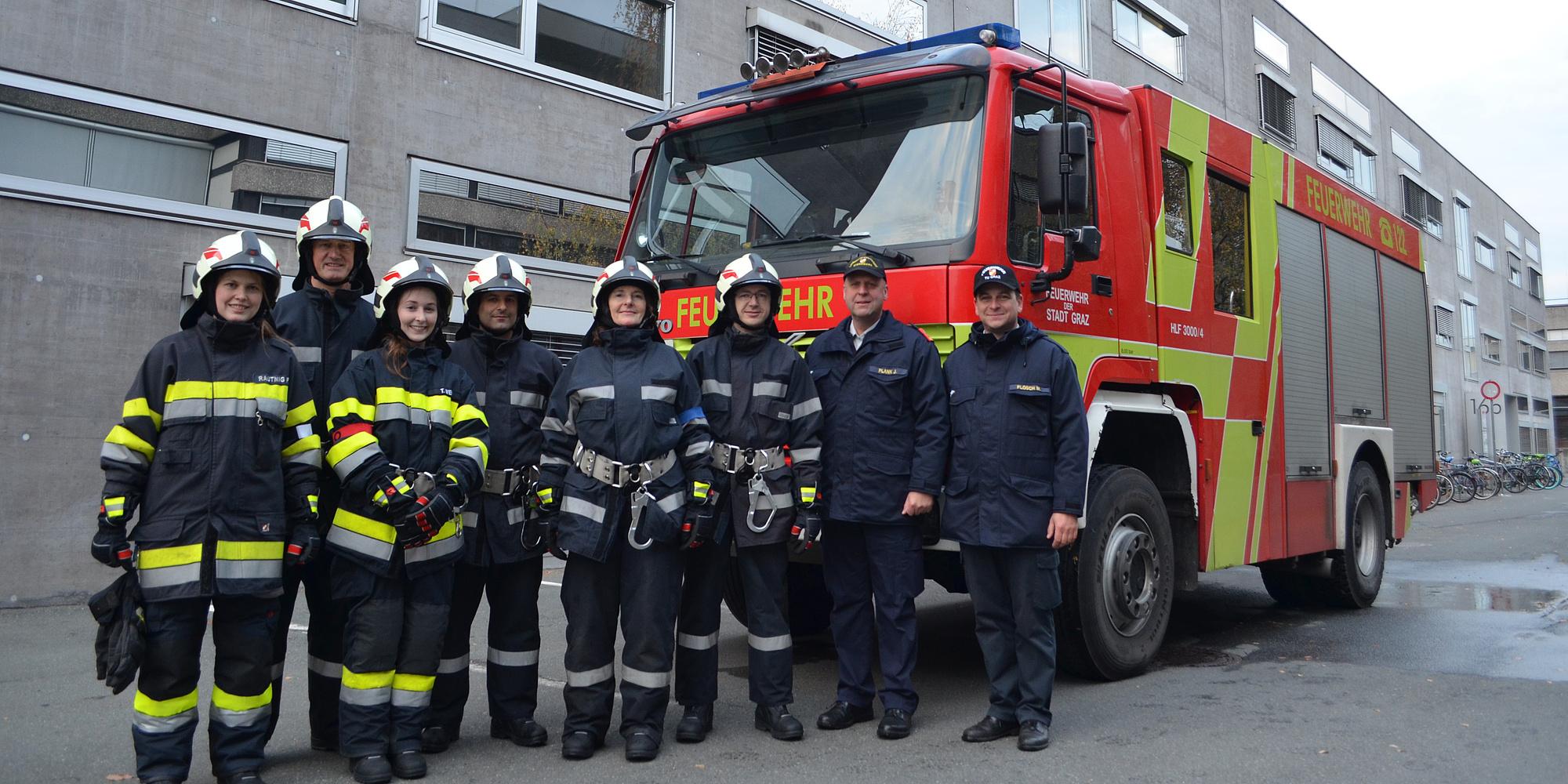 Kameradinnen und Kameraden der Freiwilligen Feuerwehr TU Graz stehen in Schutzkleidung vor einem  Feuerwehrfahrzeug.