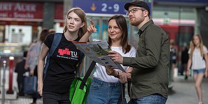 Two female students one of whom is pointing and one male student stand at the railway station and orientate themselves using a map.
