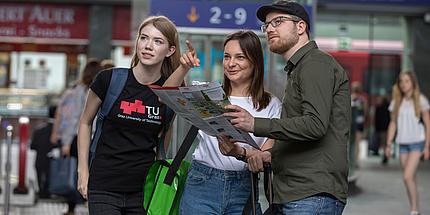 Zwei Studentinnen und ein Student stehen am Bahnhof und orientieren sich mithilfe eines gedruckten Plans und der Anzeigen.