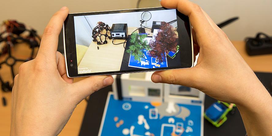 Ein Smart-Phone wird von zwei Händen gehalten. Am Bildschirm zu sehen ist die Visualisierung eines Versuchaufbaus am Know-Center