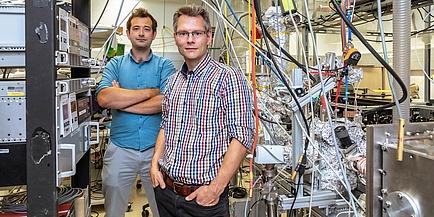 Zwei TU Graz Forscher in einem Physiklabor inmitten von Kabeln und Geräten