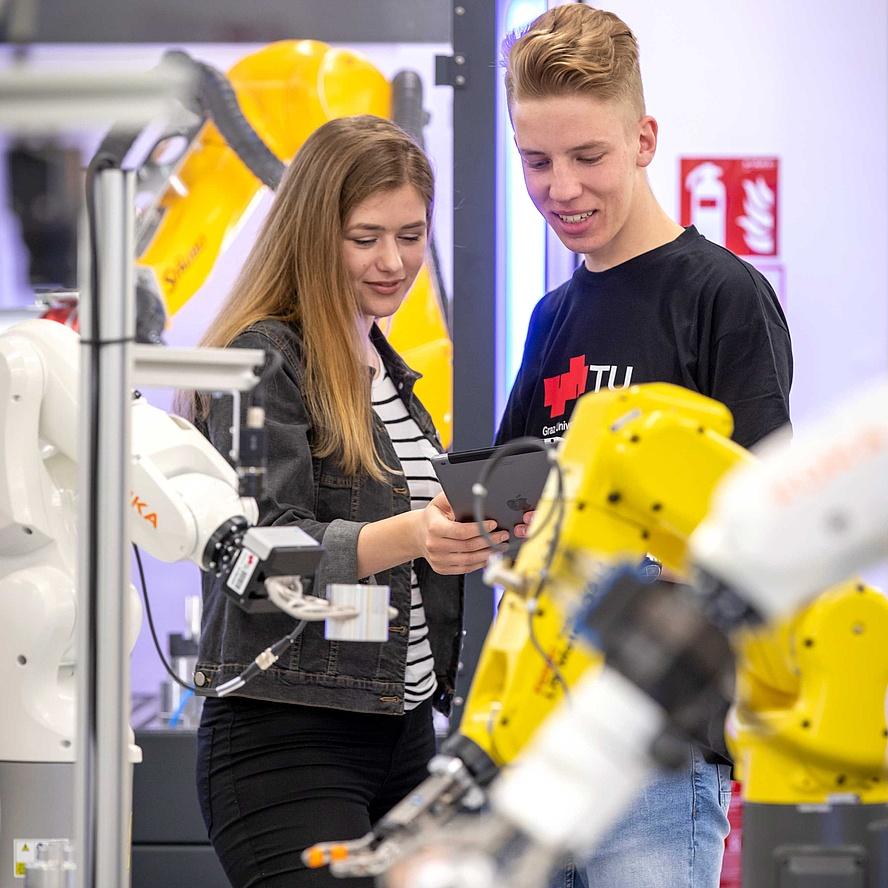 2 junge Leute zwischen Maschinen