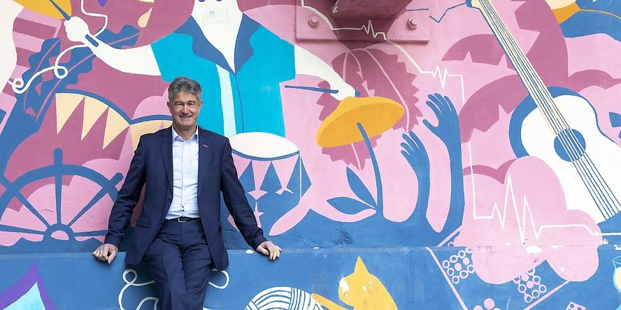 Mann im Anzug vor knallbunter Wand.