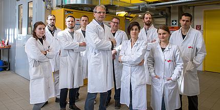 Mehrere Personen stehen in weißen Labormänteln mitten in einem Labor.