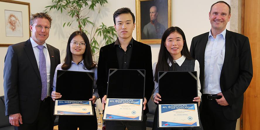 Zwei chinesische Studentinnen und ein chinesischer Student halten Ihre Stipendienurkunden in die Kamera, umringt von zwei Herren.
