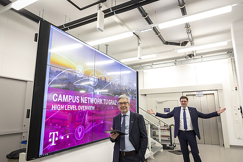 Two TU Graz researchers stand next to a monitor wall