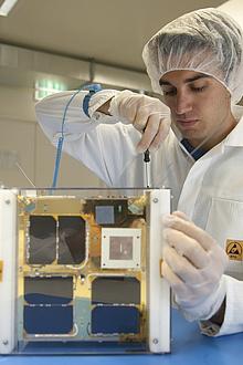 Wissenschaftliche Mitarbeiter/in beim Bau von TUGSAT-1 im Reinraum an der TU Graz.