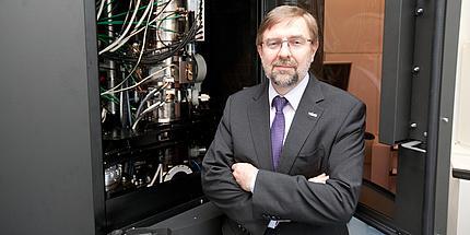 Institutsleiter Ferdinand Hofer steht mit verschränkten Händen vor dem geöffneten Elektronenmikroskop