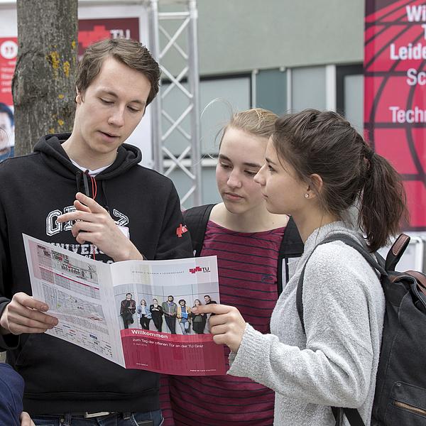Ein junger Mann zeigt zwei Schülerinnen den Weg am Campus der TU Graz.