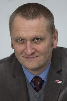 Gernot Müller-Putz sitzt auf einem Tisch, vor ihm das Modell eines Schädels und einer Hand.