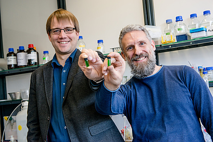 Zwei lächelnde Männer mit grün gefüllten Glasfläschchen.