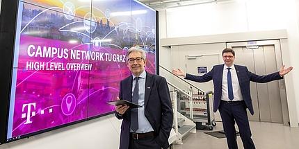 Zwei TU Graz-Forscher vor einem überdimensional großen Bildschirm