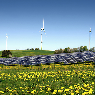 Auf einer Wiese stehen Windräder und eine Solaranlage.