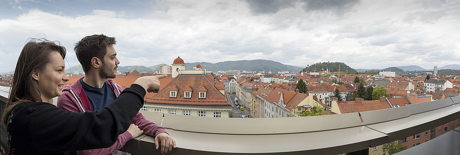 View from a terrace over the rooftops of Graz including the Schlossberg hill and distant mountains. Front left are a male and female student enjoying the view.