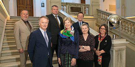 Auf der Treppe vor der Aula der Alten Universität stehen im Vordergrund drei Frauen, im Hintergrund drei Männer, die in die kamera lächeln.