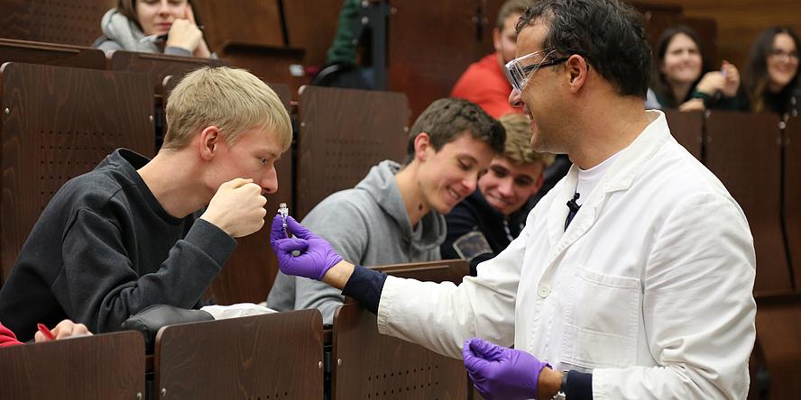 Ein Mann in Labormantel und Handschuhen reicht einem Studenten eine Riechprobe.