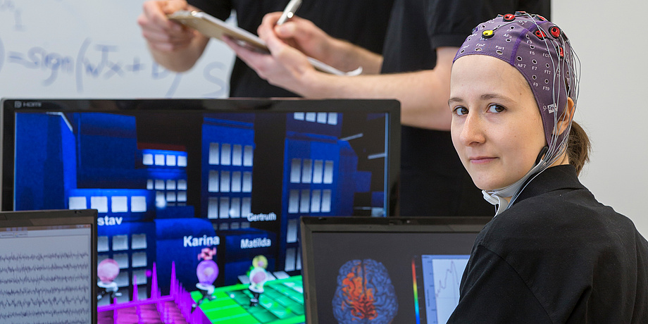 Woman with electrode cap in front of computer screens with games