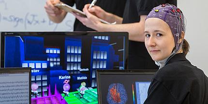 Frau mit Elektrodenhaube vor Computerbildschirmen mit Spielen