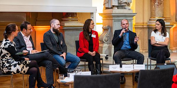 Drei Frauen und drei Männer sitzen auf Stühlen in einem Halbkreis. Einer der Männer spricht in ein Mikrofon.