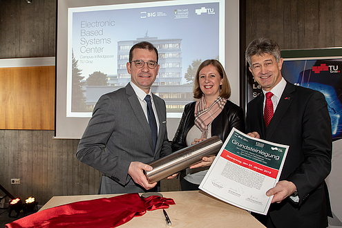 Two men and a woman hold a metal roll and a foundation stone laying certificate in the camera.