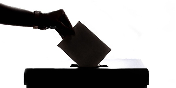A hand throws a note into a ballot box.