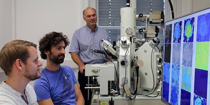 Zwei Männer sitzen an einem großen Computerbildschirm auf dem mehrere bunte Flecken zu sehen sind. Ein weiterer Mann steht hinter einem großen weißen Gerät mit vielen Zylindern und Schläuchen.