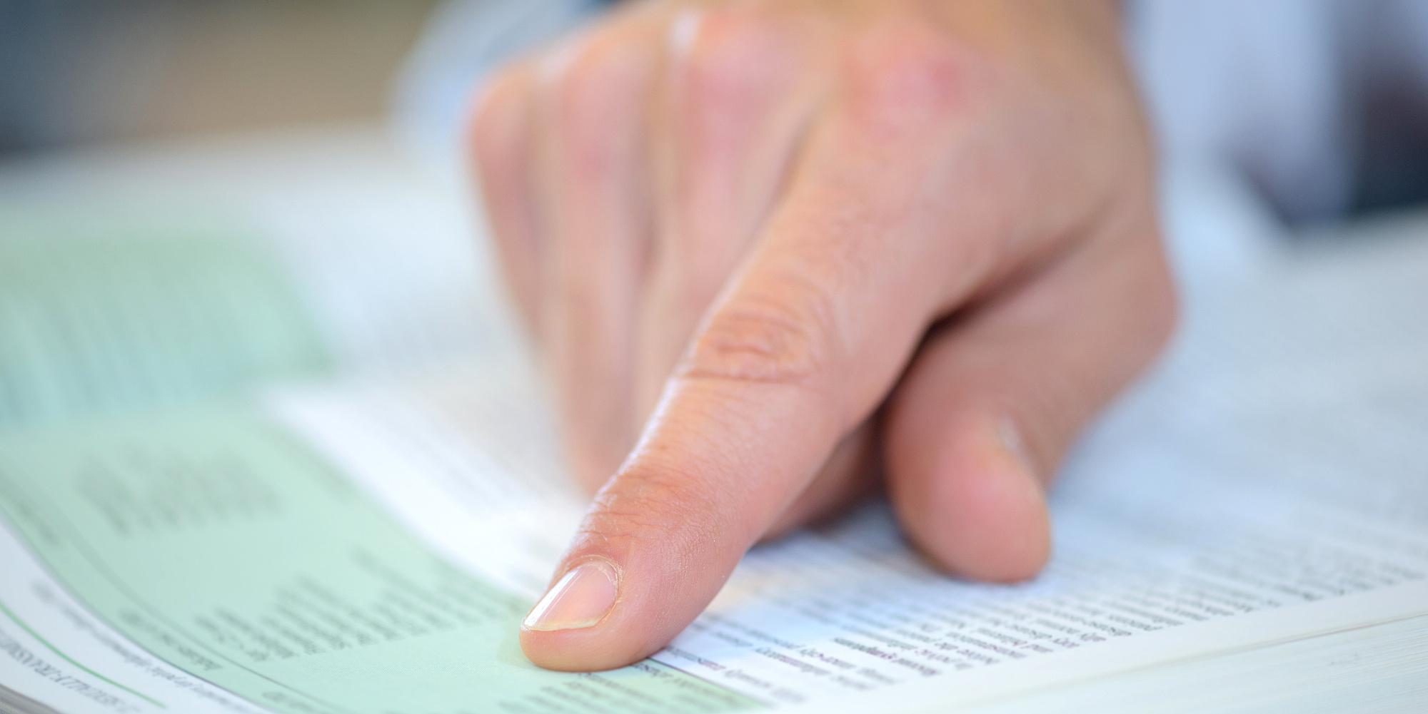 Eine Hand auf einer Buchseite.
