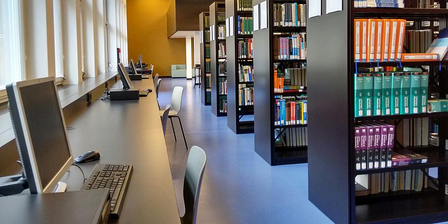 Leerer Gang zwischen Bücherregalen und ebenfalls leeren Arbeitsplätzen in einer Bibliothek