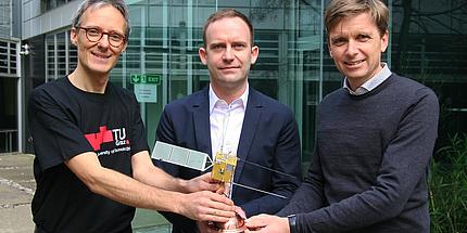 Drei Männer halten gemeinsam ein Satellitenmodell in Händen und blicken in die Kamera.