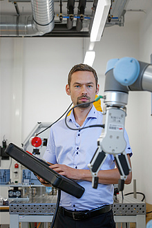 [Translate to Englisch:] TU Graz researcher operates collaborative robot arm