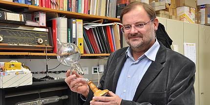 Gernot Pottlacher steht in seinem Büro und hält eine Glasröhre in der Hand.