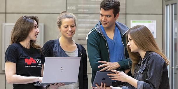 Drei junge Frauen und ein junger Mann blicken auf einen aufgeklappten Laptop und ein Tablet.