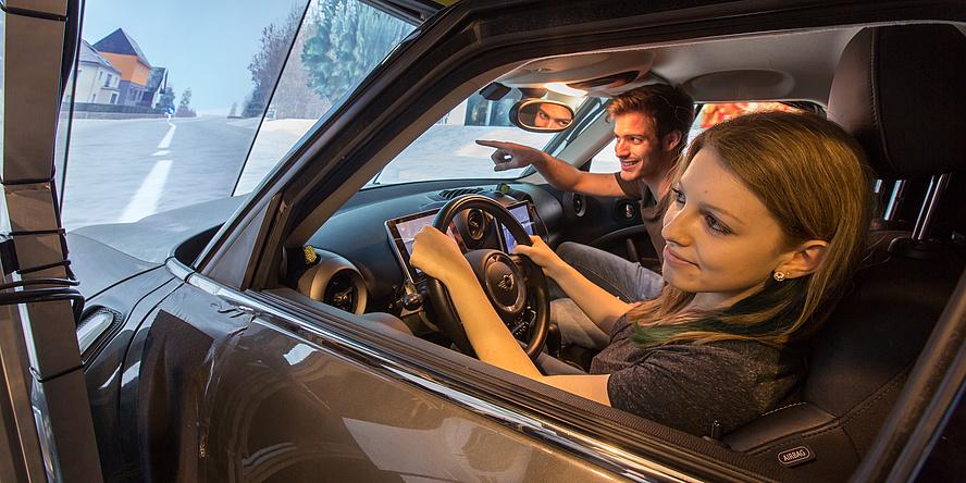 Im Fahrsimulator: Eine Frau sitzt am Steuer eines Fahrzeuges. Ein Mann sitzt neben ihr und deutet auf die Straße, die auf einem Bildschirm dargestellt ist.